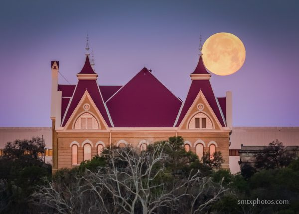 The full moon sets behind Old Main at Texas State University.