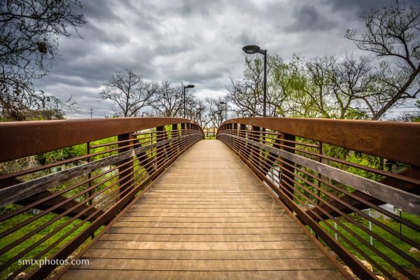 Bridge over the San Marcos River set against stormy skies.