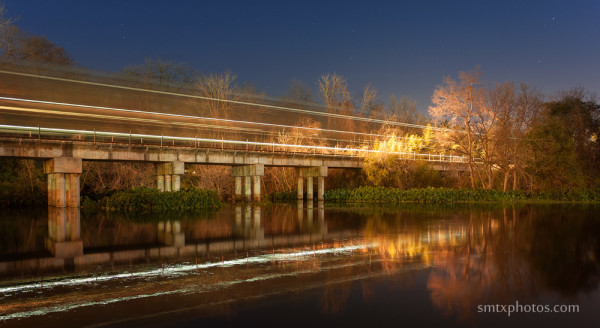 A late night train crosses over the San Marcos River near Rio Vista Park.