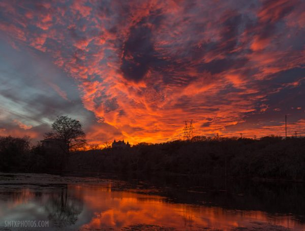 A fiery sunset over Spring Lake and Old Main in San Marcos, TX