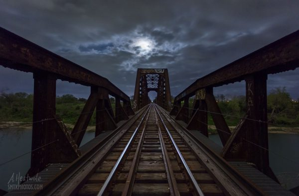 The full moon rises over a train trestle on the Blanco River.