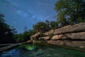 Shooting stars from the Perseid Meteor Shower streak overhead a Jacob's Well.