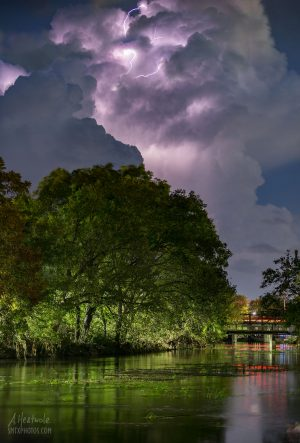 Lightning flashing from a massive thunderhead over the San Marcos River.