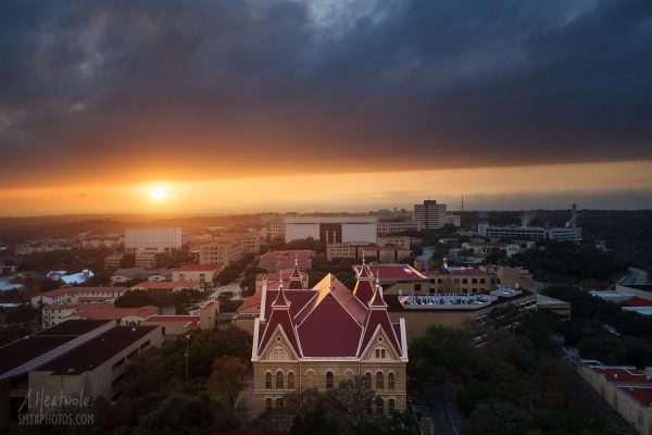 The setting sun blazes through a gap in the heavy clouds behind Old Main and Texas State University.
