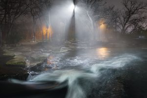 Lights shine through the fog on the San Marcos River at Rio Vista.