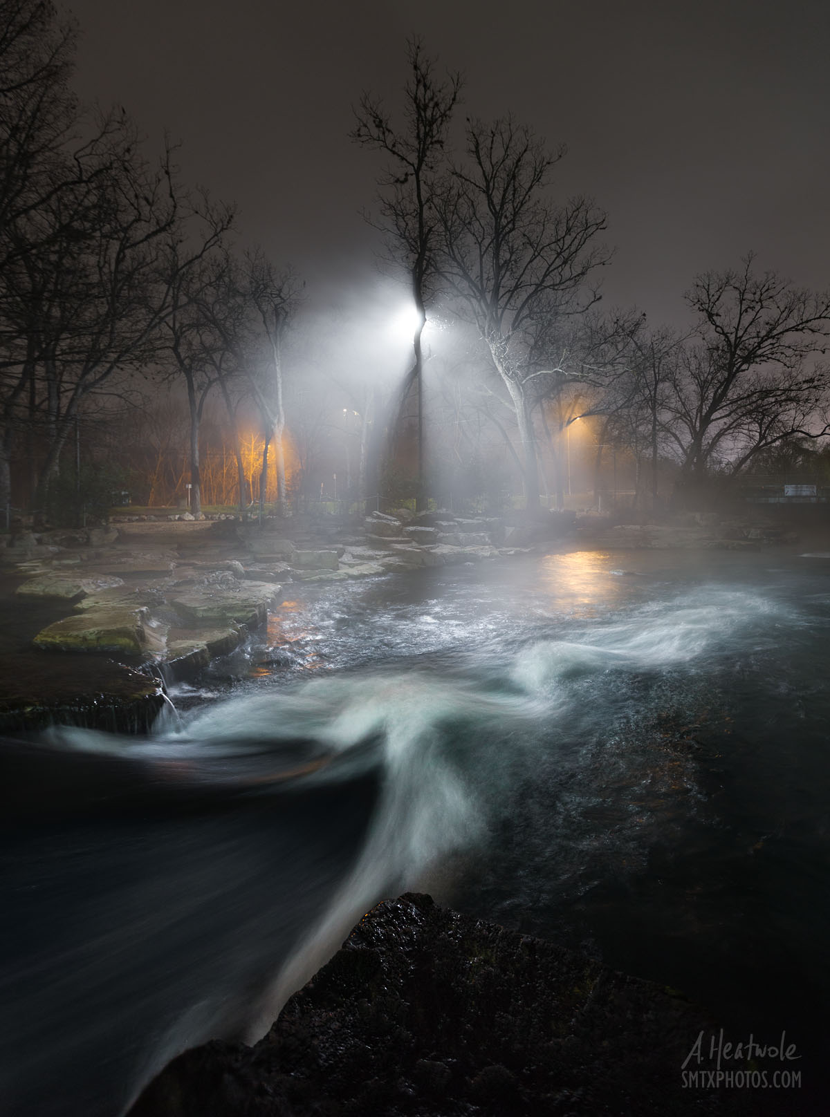 Lights shine through the fog on the San Marcos River at Rio Vista Dam.