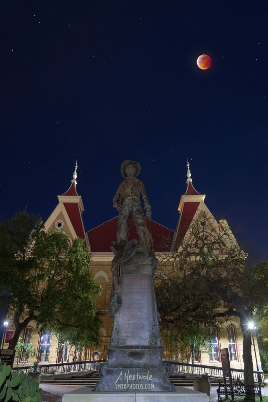 The blood moon glows red above Old Main at Texas State University.
